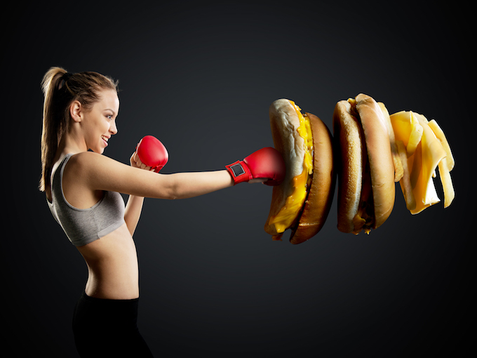 Fit, young, energetic woman boxing unhealthy food, black background