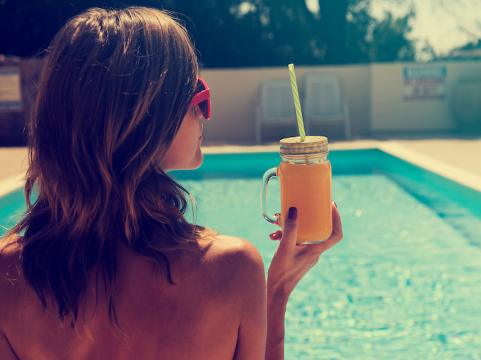 Woman on the swimming pool holding jar with orange juice.